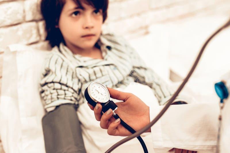 Piccolo ragazzo malato che fa la sua controllare pressione sanguigna fotografie stock