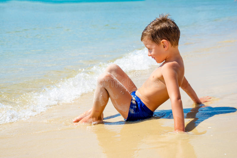 Piccolo ragazzo solo che si siede sulla spiaggia vicino all'acqua fotografia stock