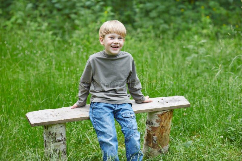 Piccolo ragazzo sorridente biondo in jeans che si siedono su un banco di parco fotografia stock libera da diritti