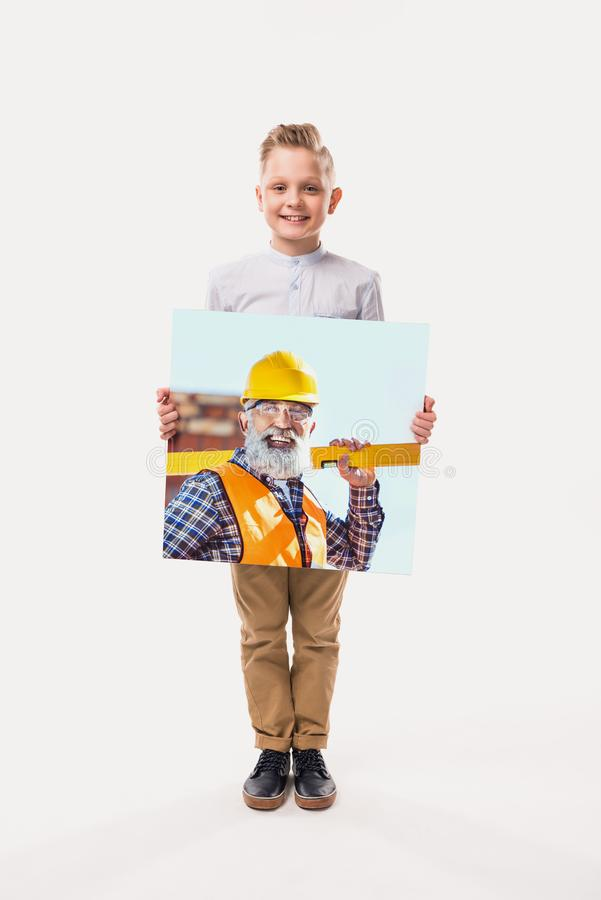piccolo ragazzo sorridente che finge di essere operaio, immagini stock