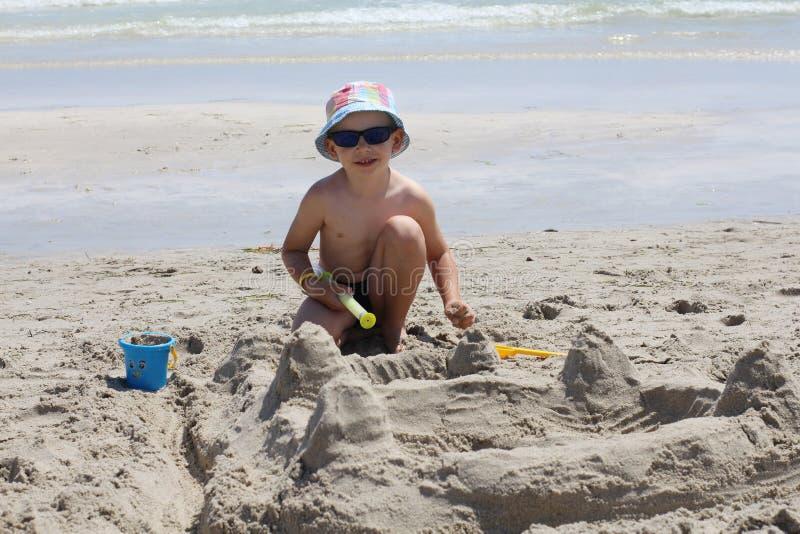 Piccolo ragazzo sveglio costruisce un castello della sabbia Camera della sabbia sulla spiaggia immagini stock