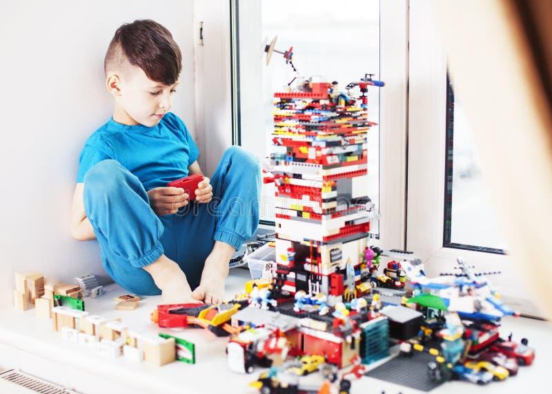 Piccolo ragazzo sveglio del bambino in et? prescolare che gioca sorridere felice dei giocattoli del costruttore a casa, fine di c fotografia stock