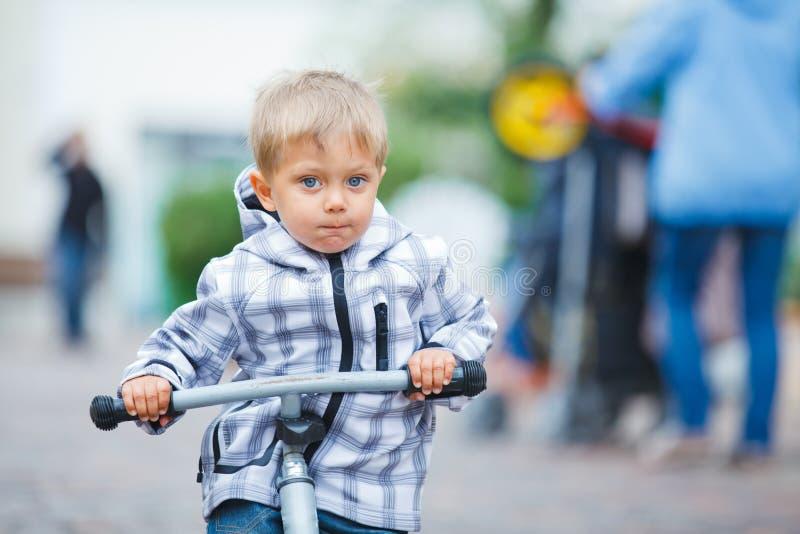 Piccolo ragazzo sveglio sulla bici in città. immagine stock libera da diritti