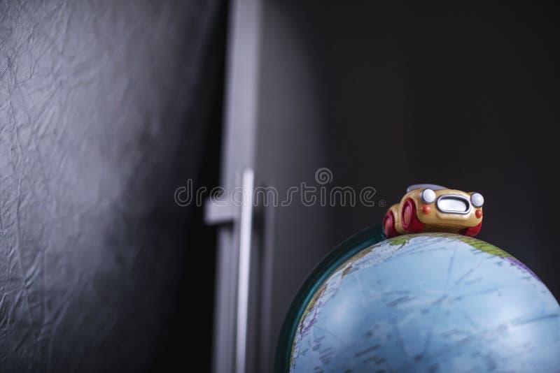 Piccolo retro giocattolo sveglio dell'automobile sul modello del globo fotografia stock