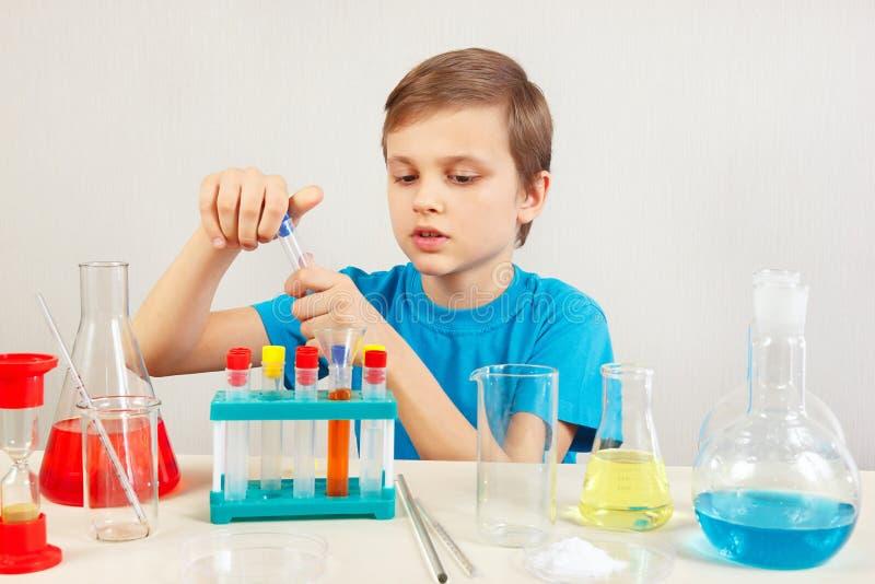 Piccolo scienziato astuto che fa gli esperimenti chimici in laboratorio fotografia stock