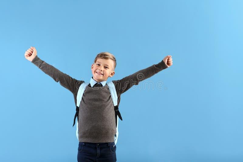 Piccolo scolaro felice con lo zaino sul fondo di colore fotografie stock