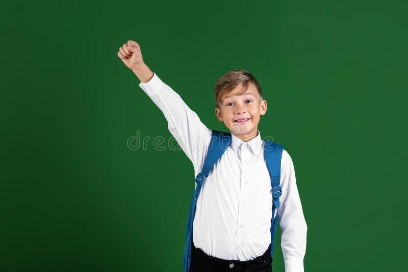 Piccolo scolaro felice con lo zaino sul fondo di colore fotografia stock