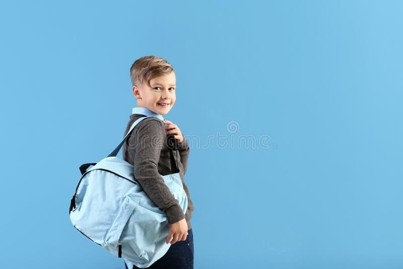 Piccolo scolaro sveglio con lo zaino sul fondo di colore fotografia stock libera da diritti