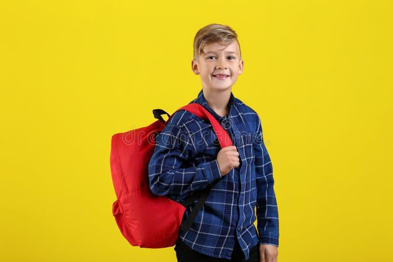 Piccolo scolaro sveglio con lo zaino sul fondo di colore fotografia stock