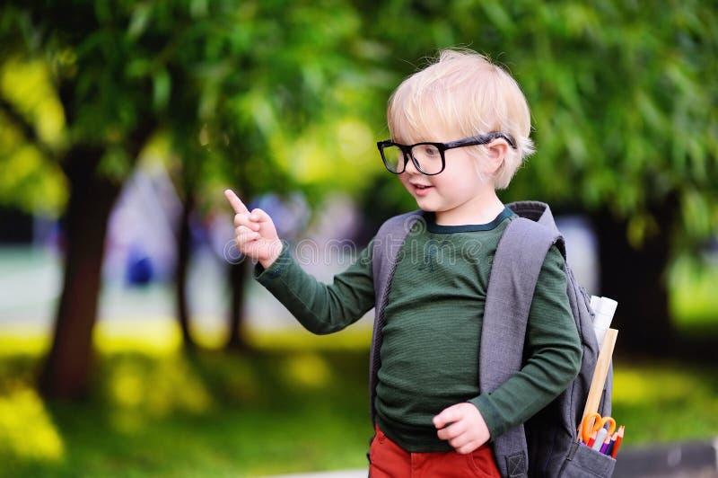 Piccolo scolaro sveglio del nerd con il suo zaino Di nuovo al concetto del banco fotografie stock