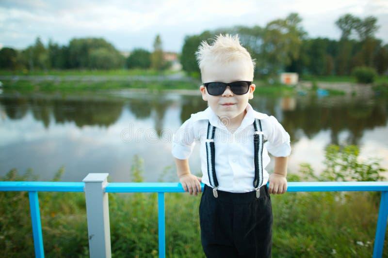 Piccolo signore con gli occhiali da sole all'aperto immagini stock libere da diritti