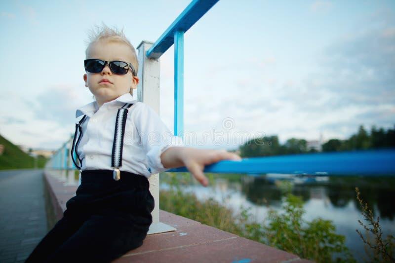 Piccolo signore con gli occhiali da sole all'aperto fotografia stock libera da diritti