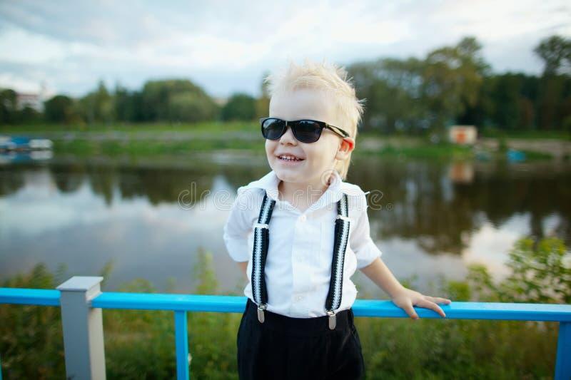 Piccolo signore con gli occhiali da sole all'aperto fotografia stock