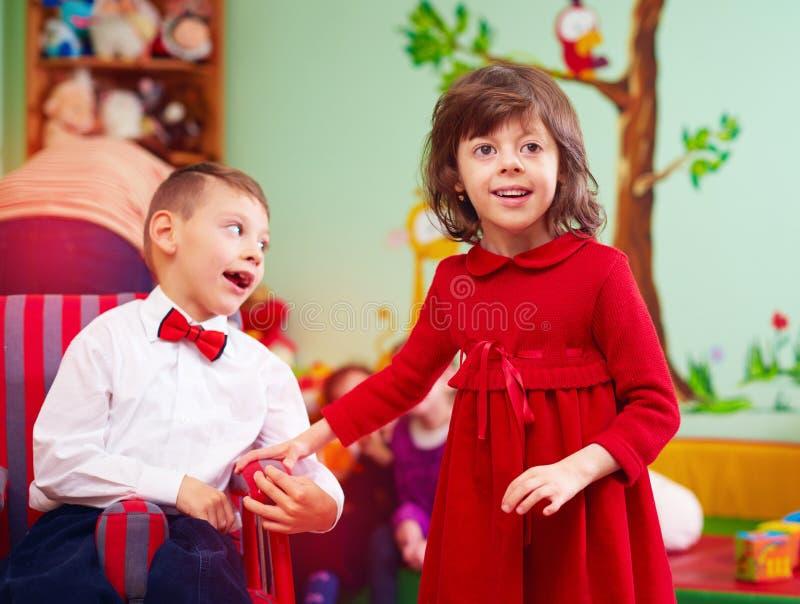 Piccolo signore sveglio in sedia a rotelle ed in signora al centro di riabilitazione per i bambini con i bisogni speciali immagine stock