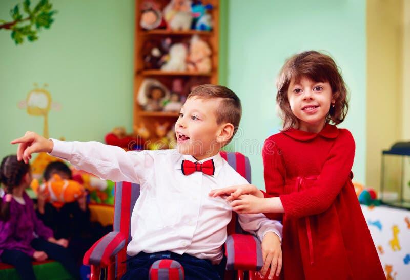 Piccolo signore sveglio in sedia a rotelle ed in signora in vacanza nell'asilo per i bambini con i bisogni speciali immagini stock libere da diritti