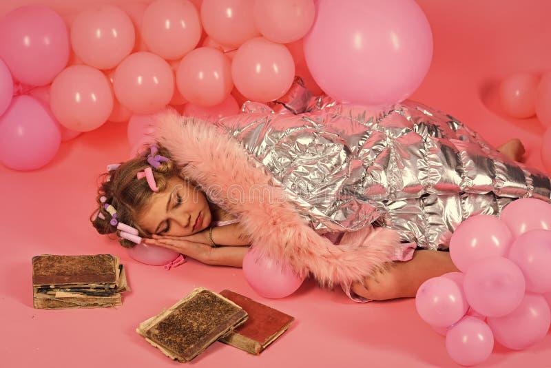 Piccolo sonno di un anno della ragazza ai vecchi libri fotografie stock