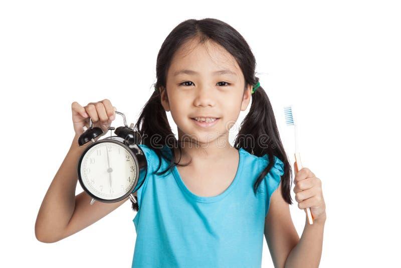 Piccolo sorriso asiatico della ragazza con un orologio e uno spazzolino da denti fotografia stock libera da diritti