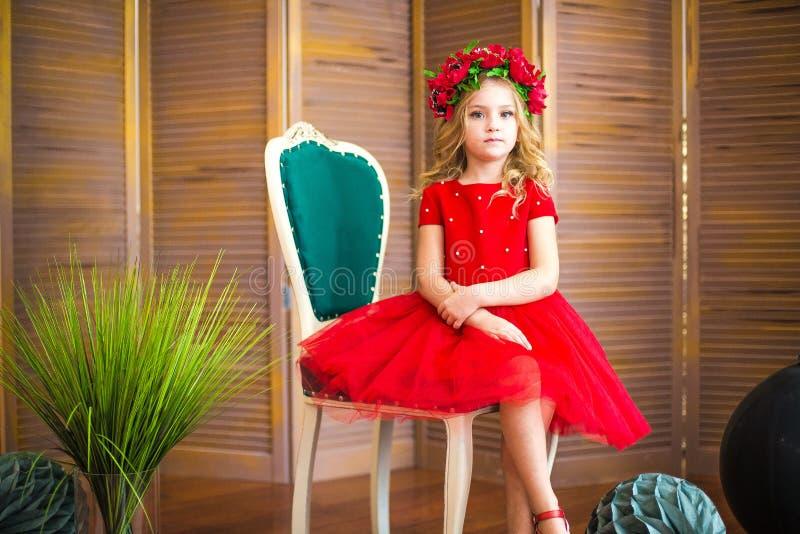 Piccolo sorriso della ragazza, modo Bambino che sorride con l'acconciatura bionda in vestito rosso Concetto del salone di bellezz fotografia stock