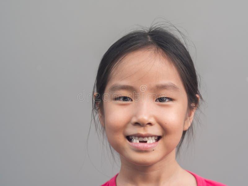 Piccolo sorriso sveglio asiatico della ragazza con il suo dente rotto fotografia stock