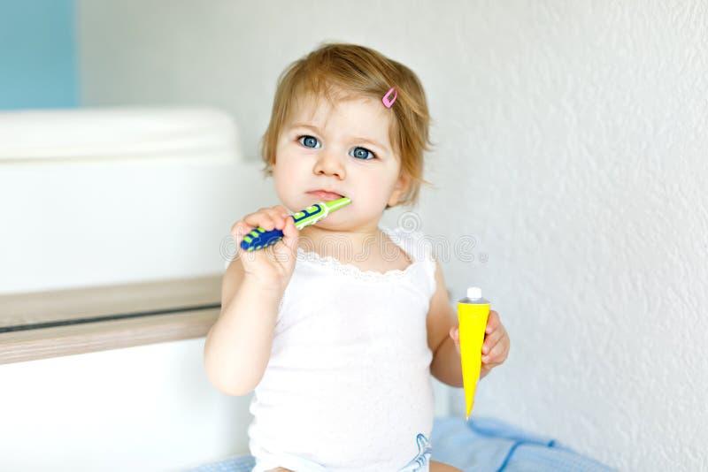 Piccolo spazzolino da denti della tenuta della neonata e primi denti di spazzolatura Bambino che impara pulire il dente di latte  fotografie stock libere da diritti