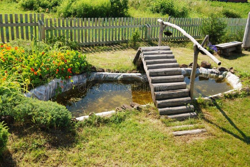 piccolo stagno del giardino con il ponticello di legno