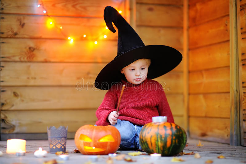 Piccolo stregone che gioca con le zucche di Halloween fotografia stock libera da diritti