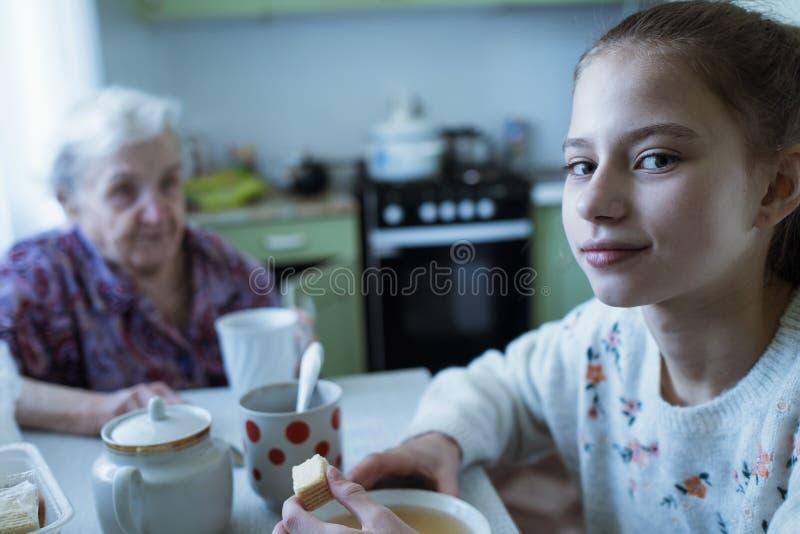 Piccolo tè bevente della ragazza dell'innamorato con sua nonna Prima colazione fotografie stock