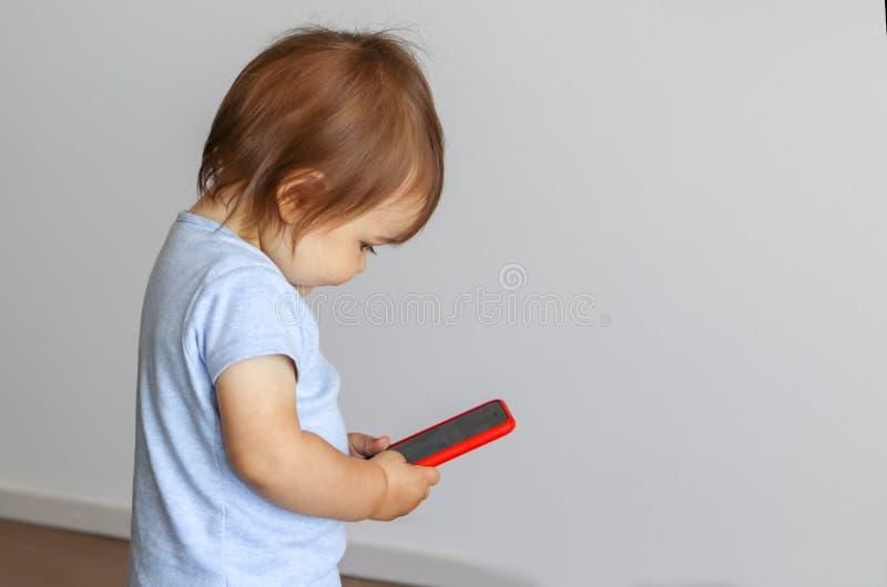 Piccolo telefono cellulare sveglio della tenuta del neonato in sue mani ed esaminare schermo fotografia stock