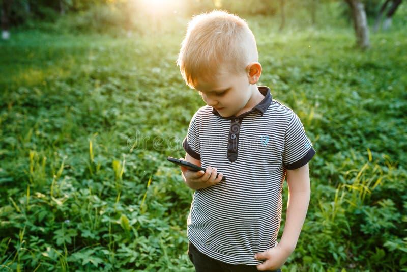 Piccolo telefono sveglio della tenuta del ragazzo nella suoi mano e sorrisi di estate g fotografie stock libere da diritti