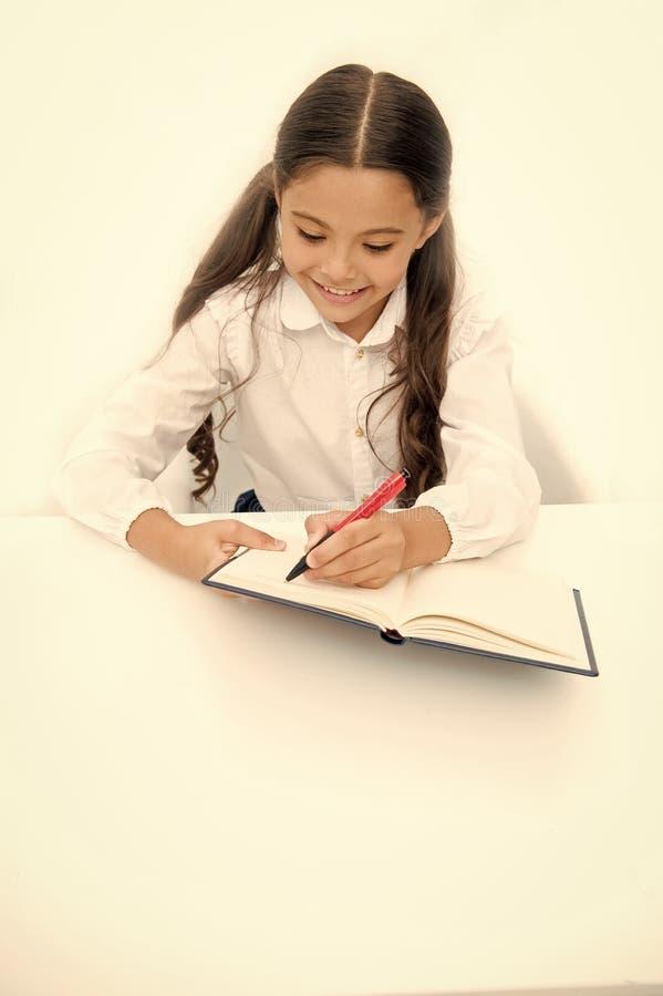 Piccolo topo di biblioteca Avvisi di scrittura Il bambino della ragazza scrive il hometask mentre sieda il fondo di bianco della  fotografia stock libera da diritti