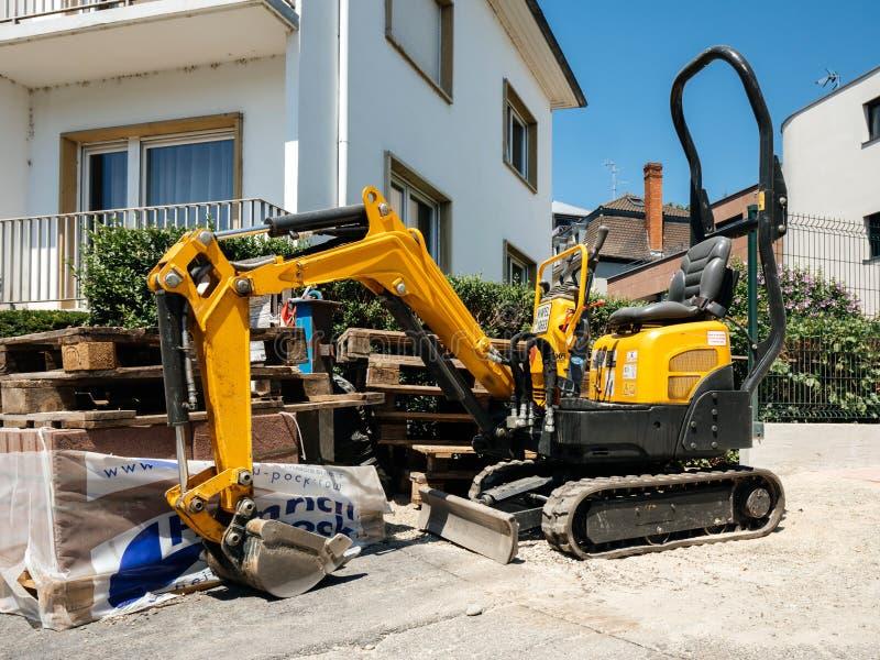 Piccolo trattore giallo dell'escavatore affittato da Kiloutou immagine stock
