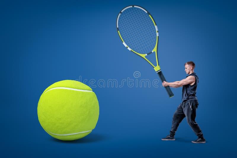 Piccolo uomo in vestiti neri di sport che tengono la grande racchetta di tennis in mani con pallina da tennis gialla su fondo blu fotografia stock