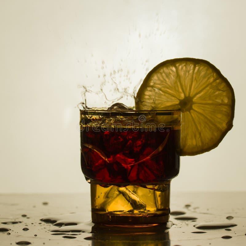 Piccolo vetro con una fetta di limone e di spruzzata fotografie stock libere da diritti