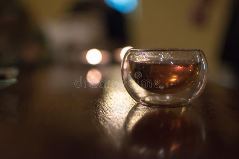 Piccolo vetro trasparente di tè nero cinese su una tavola, colpo co immagine stock libera da diritti