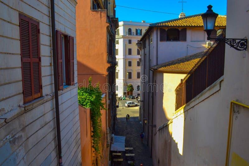 Piccolo vicolo nel mezzo di Roma, Italia, con una barra del caffè con la tavola fotografie stock libere da diritti