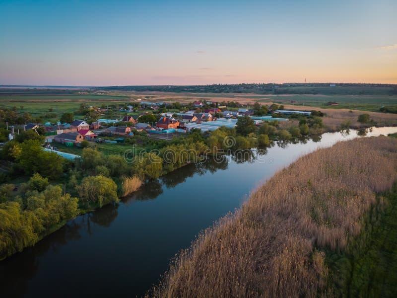 Piccolo villaggio accogliente dal lato del fiume Bello paesaggio con una vista dell'occhio del ` s dell'uccello su una sera di es fotografia stock libera da diritti
