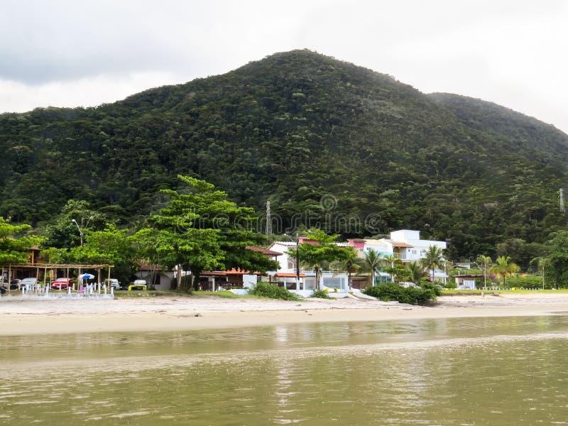 Piccolo villaggio dal mare con la spiaggia e la montagna fotografia stock libera da diritti