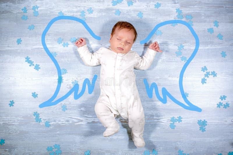 Piccolo volo sveglio del bambino di sonno con le ali di angelo sopra fondo di legno Neonato con le ali dipinte di angelo immagine stock