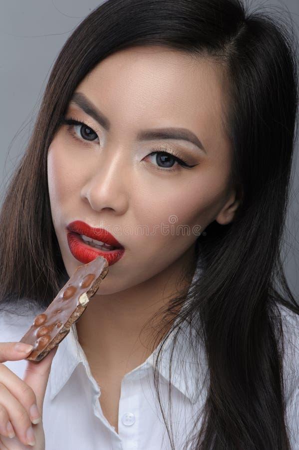 Pice asiático novo bonito comer da mulher do chocolate imagem de stock