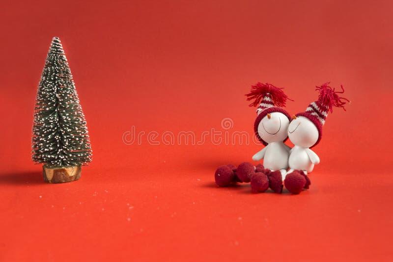 Picea artificial, verde, 2 muñecos de nieve del juguete en fondo rojo fotos de archivo
