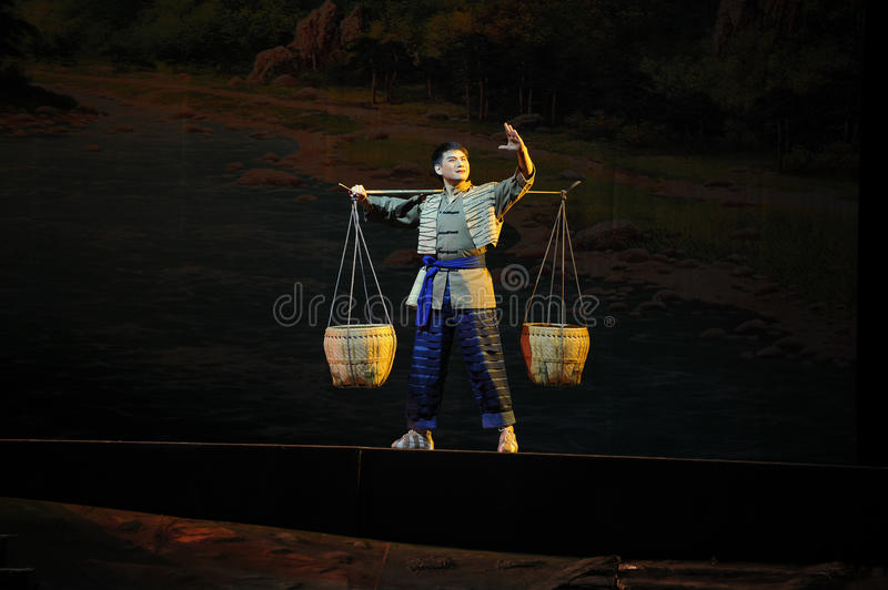 Pick a burden tramp over mountains and through ravines- Jiangxi opera a steelyard. Jiangxi opera a steelyard is adapted from a true story: the last century stock images