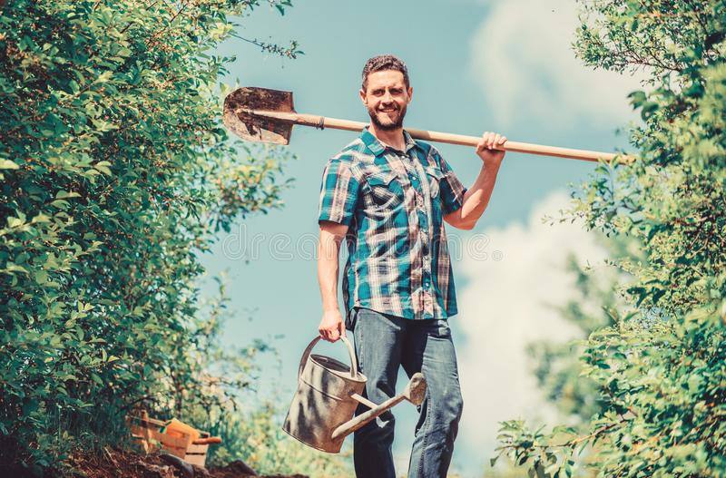 Pick out flats favorite plants. Gardening pro tips. Spring gardening. Man bearded hipster hold shovel and watering can stock photo