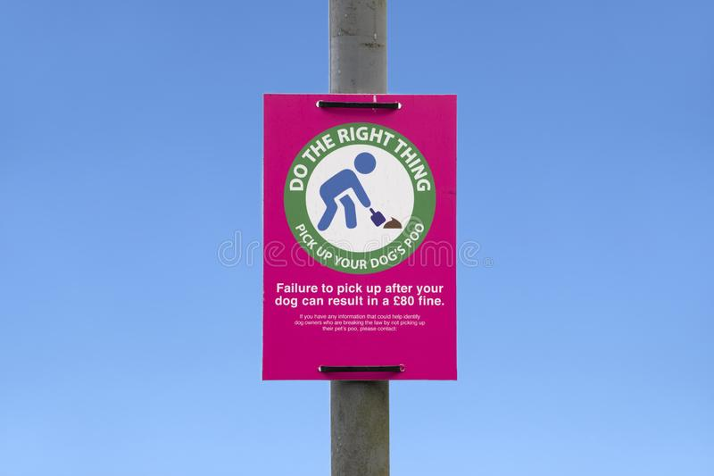 Pick up dog poo with bag pink sign and blue sky stock photos