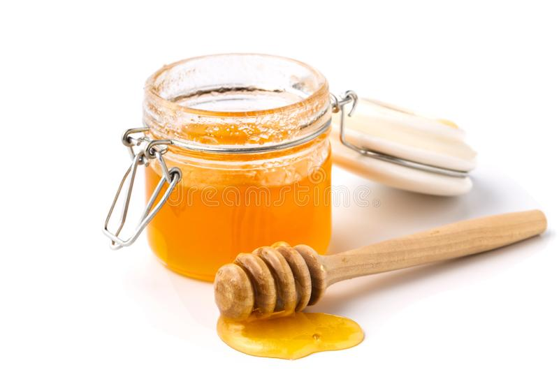 Pick up the honey jar and pour honey, isolated stock photo