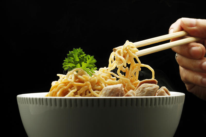 Pick up a noodle from bowl stock image