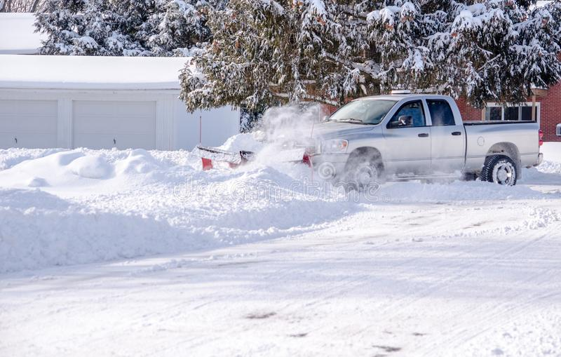 Pick-up truck with a snow blade at work stock photos
