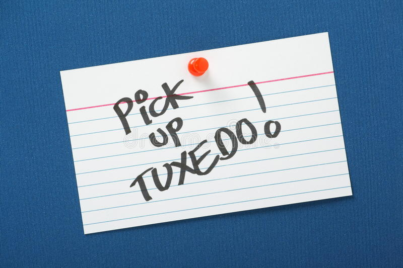 Pick Up Tuxedo. A reminder to Pick Up Tuxedo written on a white note card and pinned to a blue notice board stock photo
