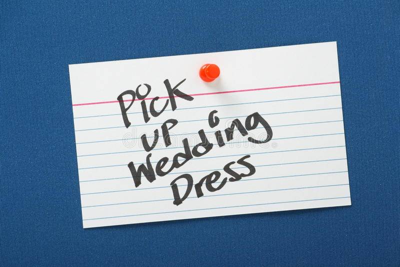 Pick Up Wedding Dress. A reminder to Pick Up Wedding Dress written on a white note card and pinned to a blue notice board stock photography