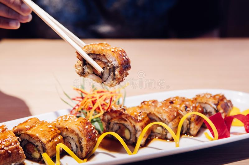 Picking Japanese grilled Unagi Maki roll with chopstick close up stock photos
