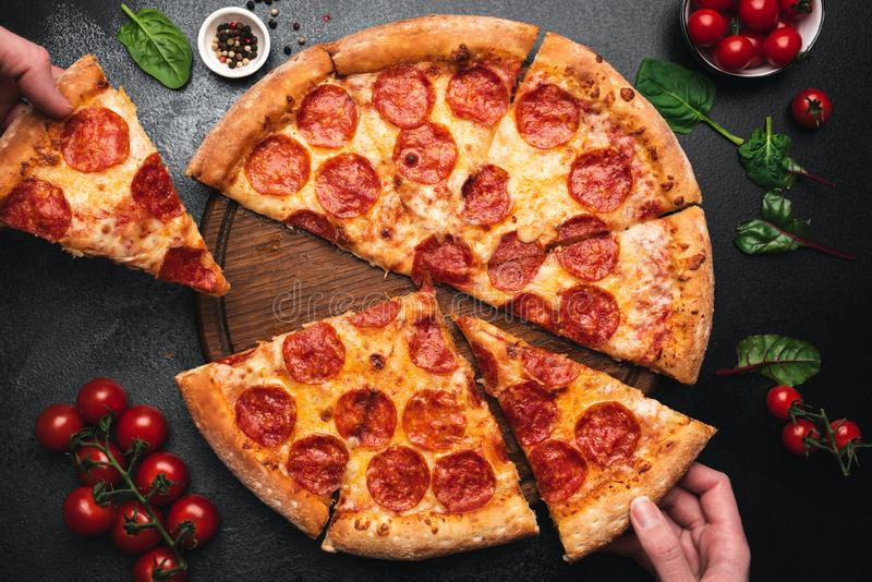 Picking slice of pepperoni pizza stock image